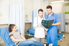 Doctors analyzing patient`s MRI scan results. Radoilogist discussing at MRI scan results with a doctor in emergency room with female patient on bed Stock Photos