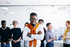 Radosna afrykanina CEO pozycja i skrzyżowanie jego ręki z kolegami Obrazy Stock