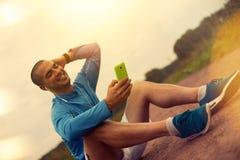 Radosna atleta po stażowego obsiadania i patrzeć smartphone Obrazy Royalty Free