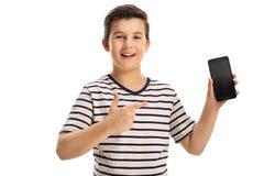 Radosna chłopiec trzyma wskazywać i telefon Fotografia Royalty Free