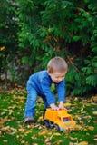 Radosna chłopiec w jesieni parkowej bawić się maszynie Zdjęcia Royalty Free