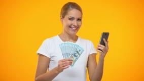 Radosna dama pokazuje dolary trzyma smartphone, online zakładu zastosowanie, kredyt zdjęcie wideo
