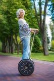 Radosna dojrzała dama cieszy się wycieczkę na nowożytnym pojazdzie Zdjęcia Royalty Free
