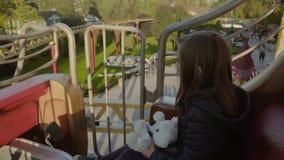 Radosna dziewczyna jedzie na carousel i ono uśmiecha się szczęśliwie w parku w jesieni w zwolnionym tempie zdjęcie wideo