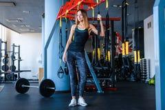 Radosna dziewczyna jest ubranym sportswear trzyma zawieszenie sprawności fizycznej patki w gym obraz royalty free