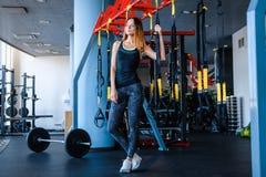 Radosna dziewczyna jest ubranym sportswear trzyma zawieszenie sprawności fizycznej patki w gym obraz stock