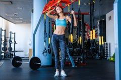Radosna dziewczyna jest ubranym sportswear trzyma zawieszenie sprawności fizycznej patki w gym zdjęcie stock