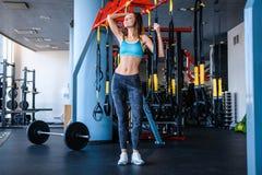 Radosna dziewczyna jest ubranym sportswear trzyma zawieszenie sprawności fizycznej patki w gym zdjęcia stock