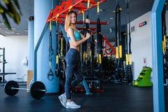 Radosna dziewczyna jest ubranym sportswear trzyma zawieszenie sprawności fizycznej patki w gym fotografia royalty free