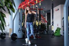Radosna dziewczyna jest ubranym sportswear trzyma zawieszenie sprawności fizycznej patki w gym fotografia stock
