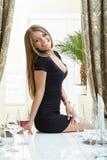 Radosna dziewczyna pozuje siedzieć na stole w restauraci Fotografia Royalty Free