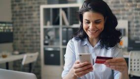 Radosna dziewczyna robi zakupy online płacić z kartą kredytową używać smartphone w biurze zbiory
