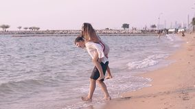 Radosna dziewczyna skacze na faceta plecy na seashore zwolnionym tempie zdjęcie wideo