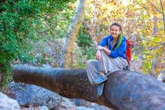 Radosna dziewczyna z plecaka i hipisa stylowym ubraniowym obsiadaniem w lesie Zdjęcie Royalty Free