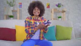 Radosna i szczęśliwa amerykanin afrykańskiego pochodzenia kobieta z afro fryzurą odpakowywa pakuneczek, siedzi na kanapie zbiory