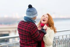 Radosna kobiet miłość data Facet robi śmieszne kobiety w czerwonym szaliku Szminek kobiety śmia się w mieście fotografia royalty free