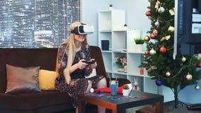 Radosna kobieta bawić się grę z joystickiem w rzeczywistość wirtualna szkłach przed TV na bożych narodzeniach zbiory