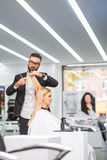 Radosna kobieta siedzi w krześle przy fryzjerem Zdjęcia Royalty Free