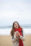 Radosna kobieta texting na smartphone przy plażą na jesieni Zdjęcia Royalty Free