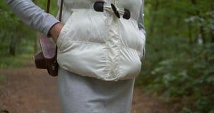Radosna kobieta utrzymuje kamerę w brąz skrzynce na jej ramieniu w drewnie zbiory