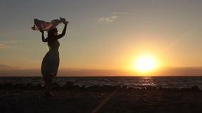 Radosna kobieta z latającym szalikiem na plaży przy zmierzchem zbiory wideo