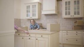 Radosna młoda rodzina błaź się wokoło w kuchni w ich nowym domu Szczęśliwa para rusza się nowy mieszkanie mąż zbiory