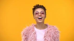 Radosna młoda kobieta w modnych eyeglasses i futerku na żółtym tle obrazy royalty free
