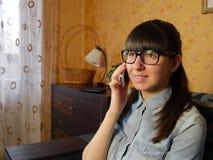 Radosna młoda kobieta opowiada na telefonie komórkowym w domu Fotografia Royalty Free