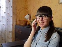 Radosna młoda kobieta opowiada na telefonie komórkowym w domu Obraz Royalty Free