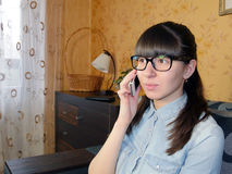 Radosna młoda kobieta opowiada na telefonie komórkowym w domu Zdjęcia Royalty Free