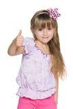 Radosna mała dziewczynka trzyma jej kciuk up Zdjęcie Royalty Free