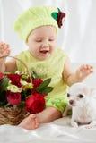 Radosna mała dziewczynka w zielonawy kapeluszowy i odzieżowym siedzi na pościeli zdjęcia royalty free