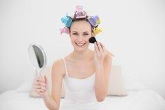 Radosna naturalna brown z włosami kobieta w włosianych curlers stosuje proszek na jej twarzy Obrazy Stock