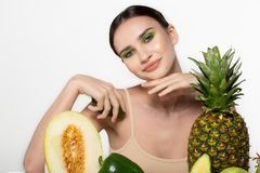 Radosna pi?kna dziewczyna z jaskrawym sztuki makeup mieniem pokraja? ?wie?ego avocado w r?ki pobliskiej twarzy, owoc w przodzie Z zdjęcie royalty free