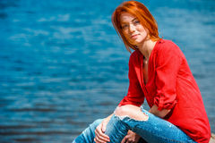 Radosna rudzielec kobieta siedzi swobodnie i ono uśmiecha się Zdjęcia Royalty Free