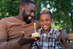 Radosna szczęśliwa chłopiec patrzeje świeczkę zdjęcie stock