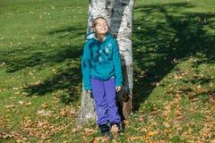 Radosna szczęśliwa mała dziewczynka opiera przeciw brzozy drzewom z zamkniętymi oczami w jesień parku Obrazy Stock