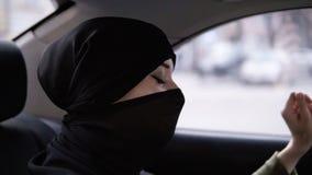 Radosna, szcz??liwa muzu?ma?ska kobieta w czarnym niqab, siedzi na tylnym siedzeniu w samochodzie, s?ucha? themusic i tanu, dobry zdjęcie wideo