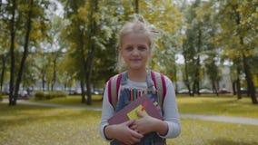 Radosna uczennica trzyma książkę zostaje w szkolnym jardzie z plecakiem Portret dosyć mądrze dziewczyny ono uśmiecha się zbiory wideo