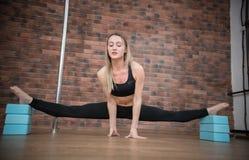 Radosna utalentowana kobieta należnie robi rozłamom w słupie tanczy studio fotografia stock