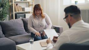 Radosna z nadwagą dziewczyna śmia się i opowiada w psychologa biurze przy sesją