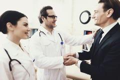 Radosne biznesmena chwiania ręki z lekarką która leczył dolegliwość przyznania obraz stock