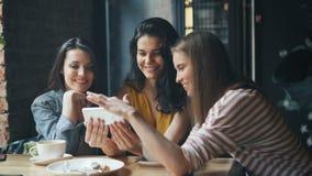 Radosne dziewczyny patrzeje smartphone parawanowy swiping ono uśmiecha się mieć zabawę w kawiarni zbiory