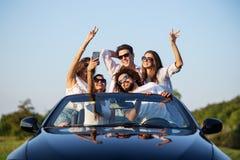 Radosne młode dziewczyny i faceci w okularach przeciwsłonecznych siedzą w czarnym kabriolecie na drogowym mieniu ręki w górę robi zdjęcia stock