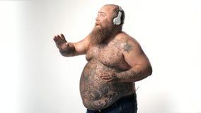 Radosnego grubego mężczyzna słuchająca piosenka i taniec zdjęcie wideo