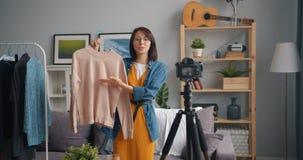 Radosnego młodej kobiety blogger magnetofonowy wideo o odziewa opowiadać gestykulować zbiory wideo