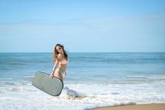 Radosnej surfingowiec dziewczyny szczęśliwy rozochocony przy ocean plaży wodą obraz stock