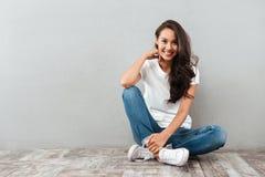 Radosny ładny azjatykci kobiety obsiadanie na podłoga obraz stock