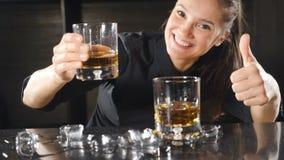 Radosny żeński barman ono uśmiecha się przy kamerą z jej kciukiem w górę Atrakcyjna dziewczyna przy baru kontuaru ono uśmiecha si zbiory
