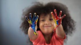 Radosny Afrykański żeński dziecko ma zabawę i pokazuje malować palmy w kamerę obrazy stock